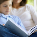 Boy reading with his mother
